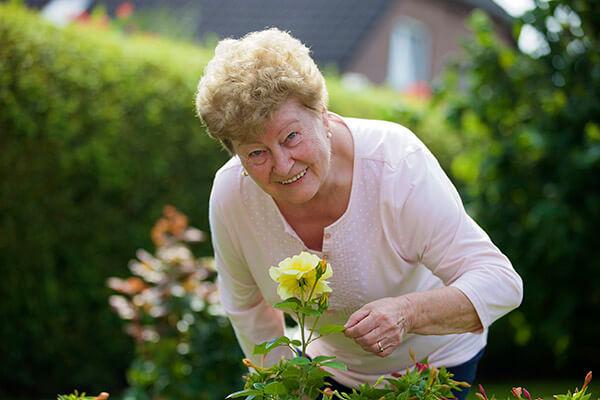 Helga Rodewald kann durch die Immobilienrente der Deutschen Leibrenten AG weiter ihren wunderschönen Garten genießen.