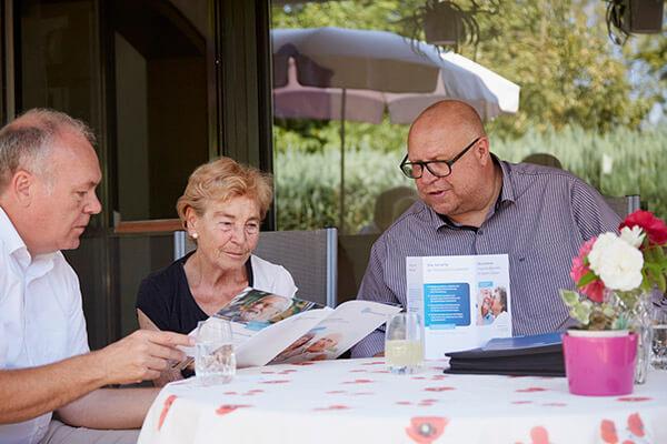 Gesprächs- und Beratungssituation zwischen Immobilienmakler und Immobilienrenten-Kundin bei Kundin vor Ort