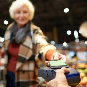 Seniorin bezahlt kontaktlos mit dem Smartphone   Mobile Pay
