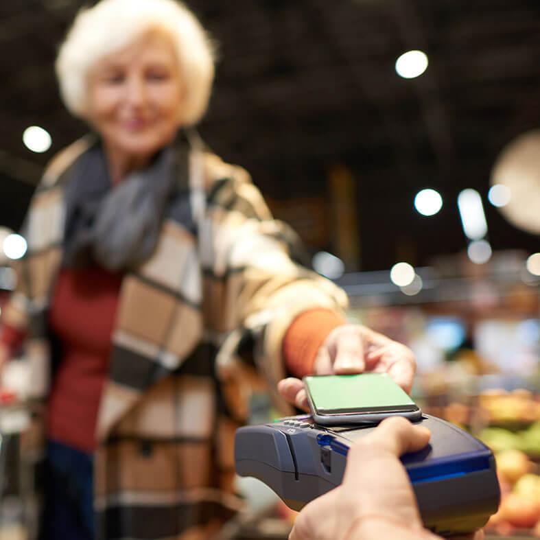 Seniorin bezahlt kontaktlos mit dem Smartphone | Mobile Pay