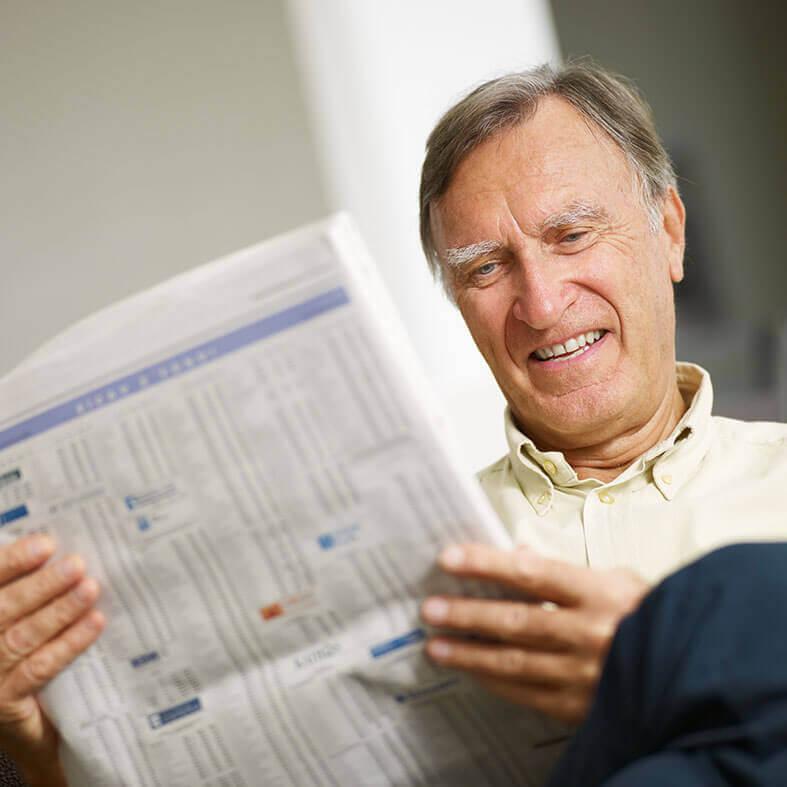 Senior studiert den Börsenteil einer Tageszeitung   Altersfinanzierung   Altersvorsorge