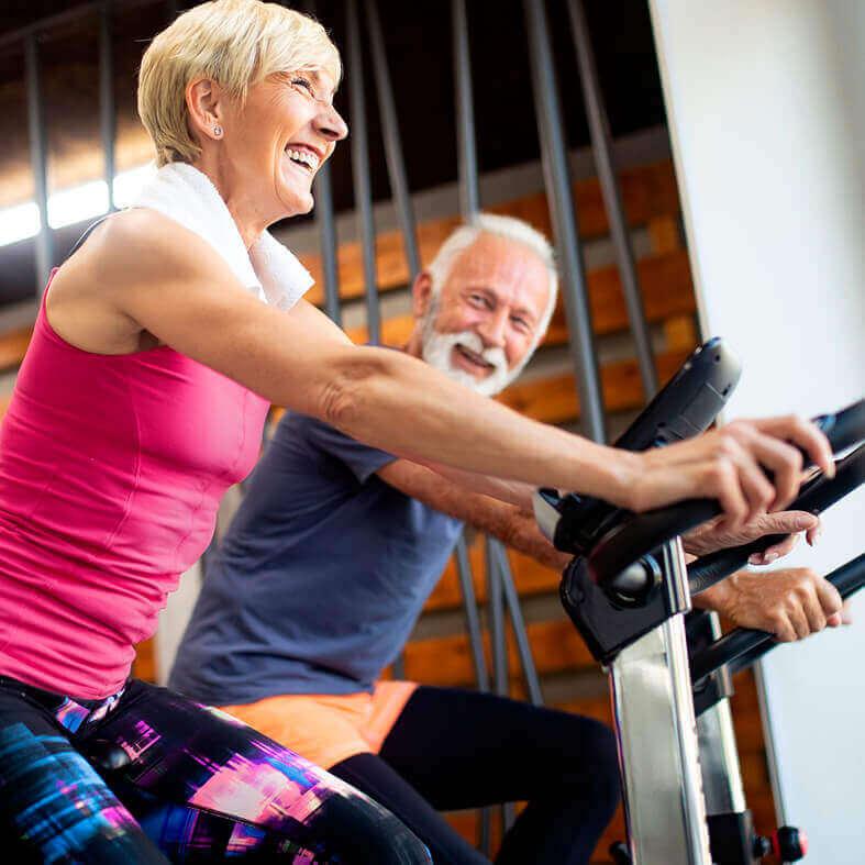 Seniorin und Senior auf Trimmrad (Fahrrad) beim Sport