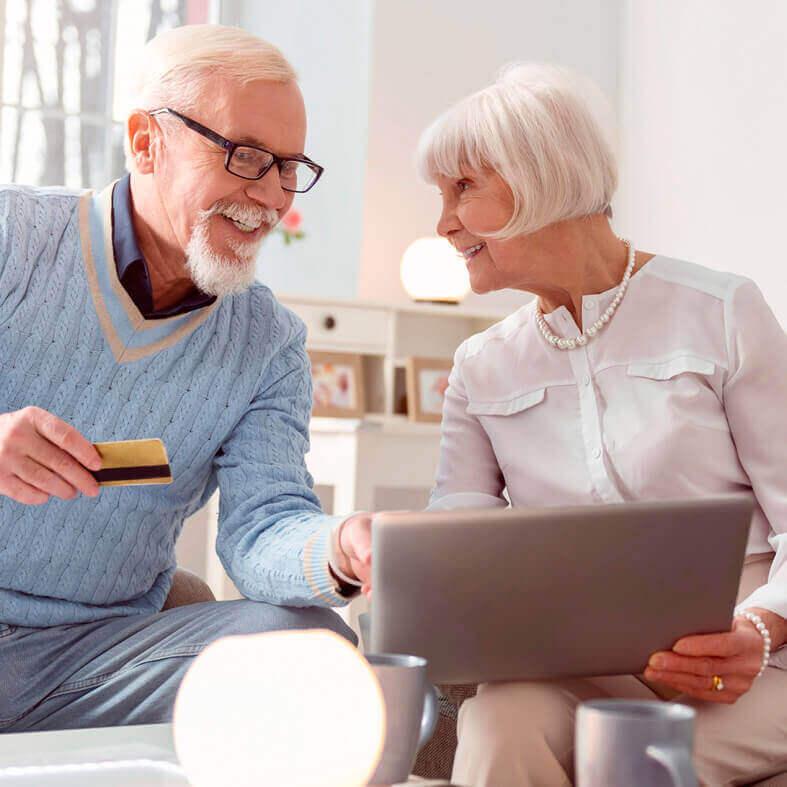 Abbildung zeigt Renter-Ehepaar beim Onlinebanking per Laptop | Deutsche Leibrenten AG