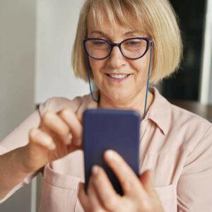 Smartphone für Senioren: Rentnerin surft an einem mordernen Smartphone