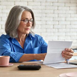 Rentnerin prüft Kreditantrag einer Bank