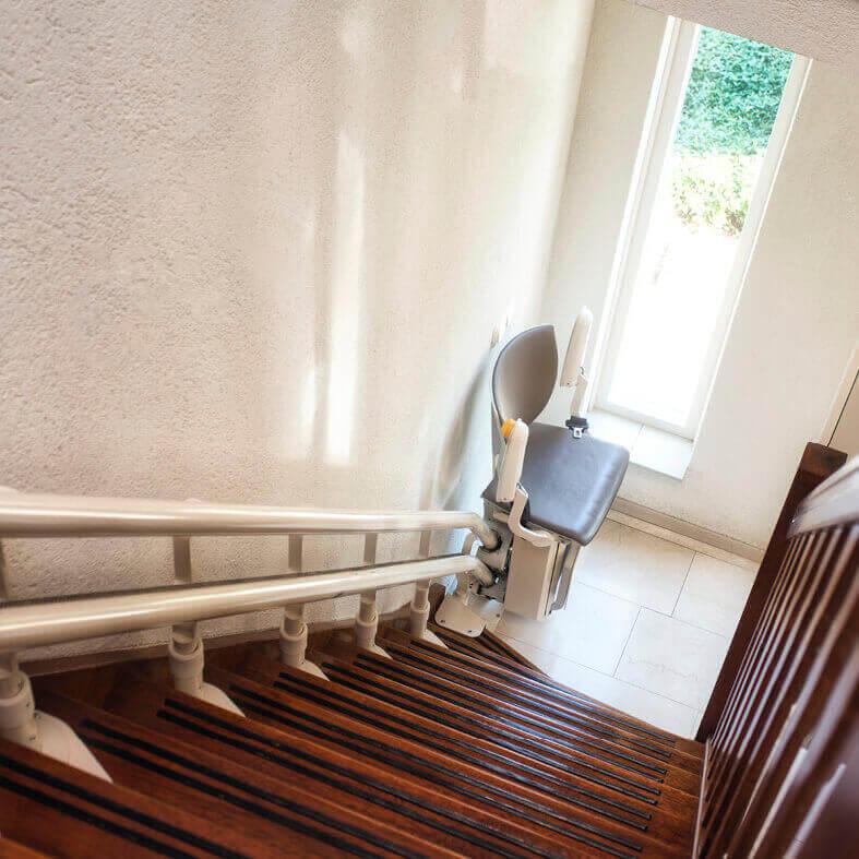 Blick eine Treppe herunter auf einen Treppenlift für Senioren