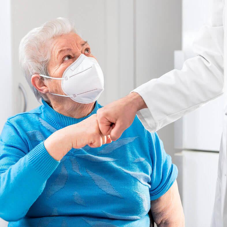 Rentnerin mit FFP2-Maske schützt sich vor Corona