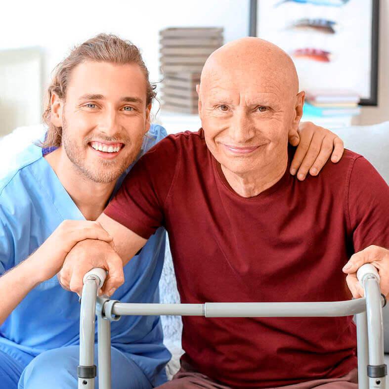 pfleger-und-senior-laecheln-in-die-kamera