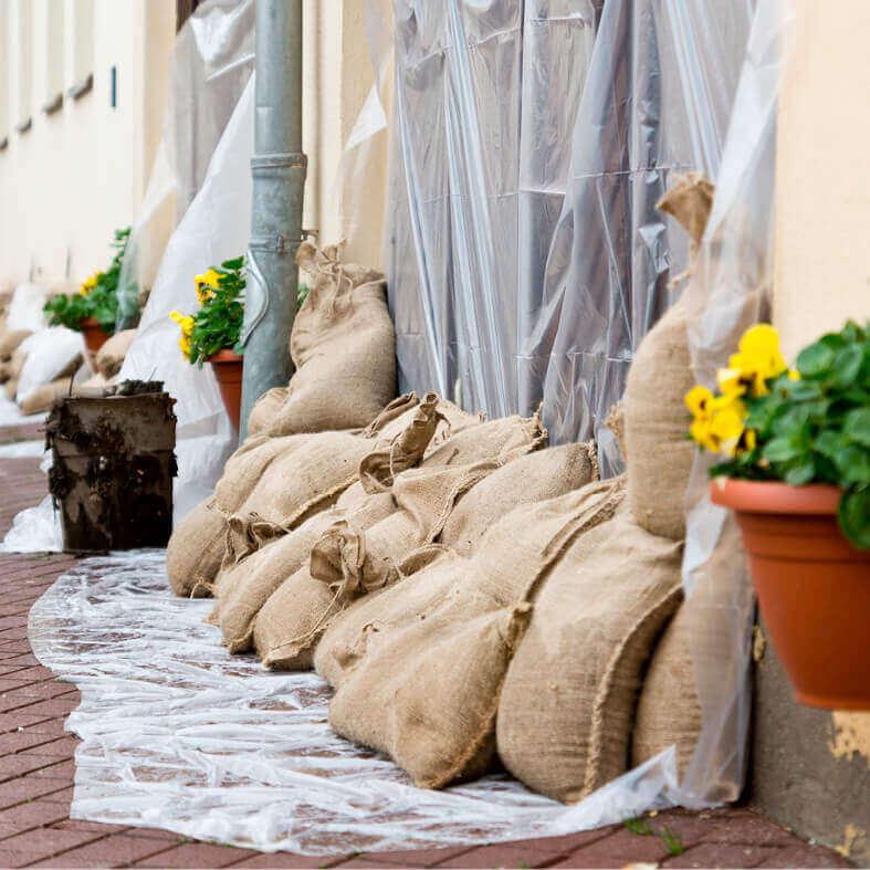 MIt Sand gefüllte Säcke vor einer Haustür zum Schutz vor Hochwasser. Wer zahlt? Die Hausrat- oder Elementarversicherung?