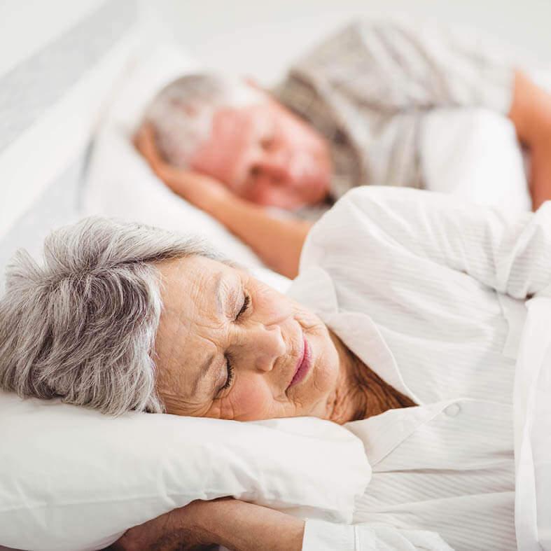 Senioren schlafen erholsam im Bett