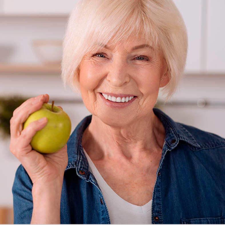 Lächelnde Seniorin hält Apfel in der Hand
