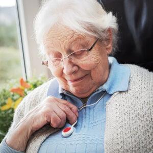 Seniorin drückt den Knopf des Hausnotrufs