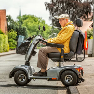Senior fährt mit Elektrodreirad über die Straße   Senioren im Straßenverkehr
