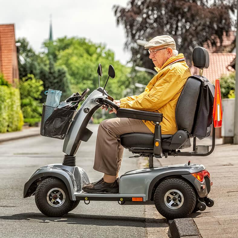 Senior fährt mit Elektrodreirad über die Straße | Senioren im Straßenverkehr